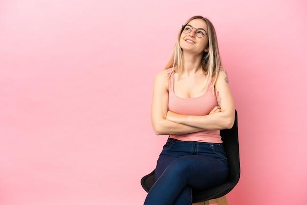 Junge frau sitzt auf einem stuhl über isoliertem rosa hintergrund und schaut lächelnd nach oben