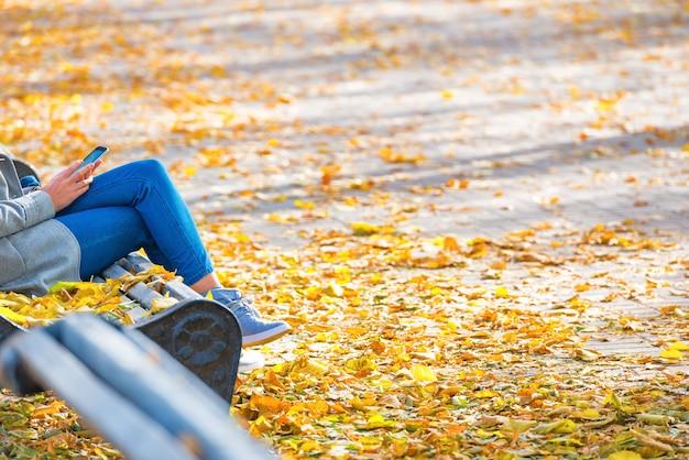 Junge frau sitzt auf einer bank im herbstpark mit gelben laub