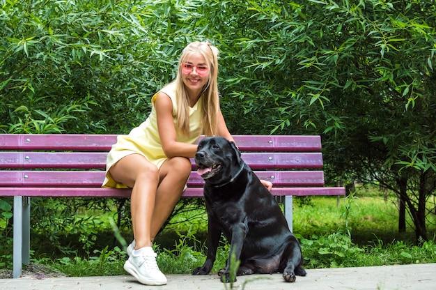 Junge frau sitzt auf einer bank in einem sommerpark mit ihrem großen schwarzen hund