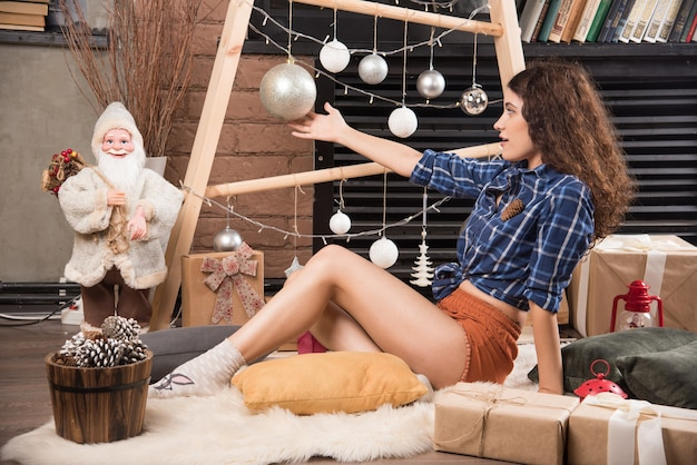 Junge frau sitzt auf flauschigem teppich mit weihnachtsschmuck