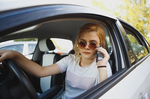 Junge frau sitzt im auto und ruft an