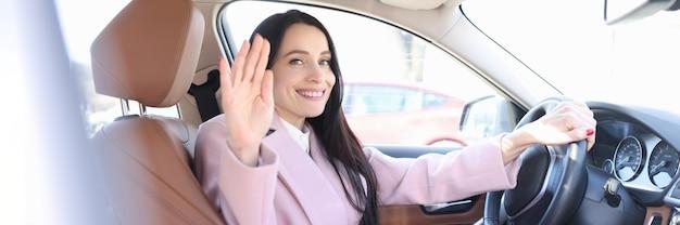 Junge frau sitzt im autosalon und winkt mit der hand
