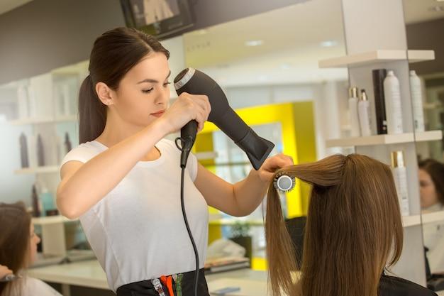 Junge frau sitzt im friseursalon frisur styling haare trocken