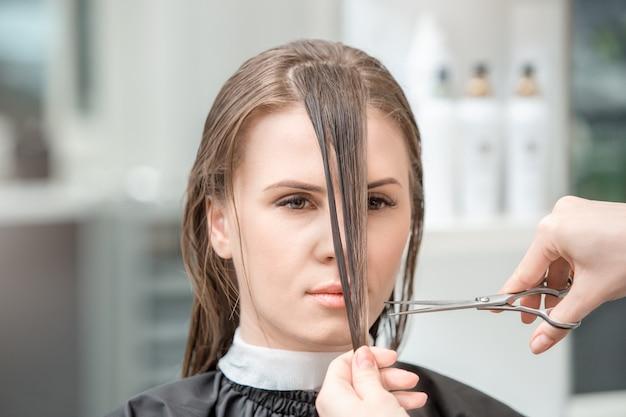 Junge frau sitzt im friseursalon frisur styling nass