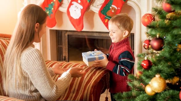 Junge frau sitzt im sessel im wohnzimmer und gibt ihrem kleinen sohn eine schachtel mit weihnachtsgeschenk