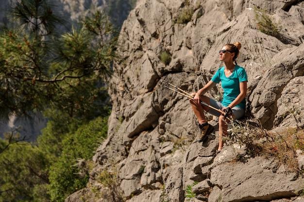 Junge frau sitzt oben auf dem berg