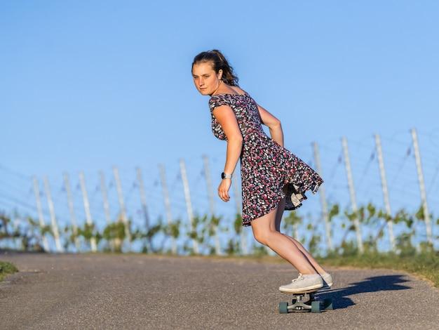 Junge frau skateboarding auf einer leeren straße, die durch grün umgeben ist