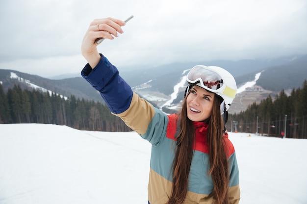 Junge frau snowboarder auf den pisten frostigen wintertag macht selfie am telefon