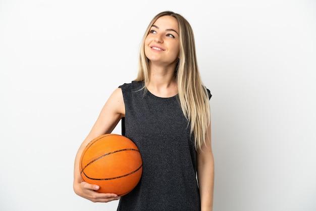 Junge frau spielt basketball über isolierter weißer wand und denkt eine idee, während sie nach oben schaut