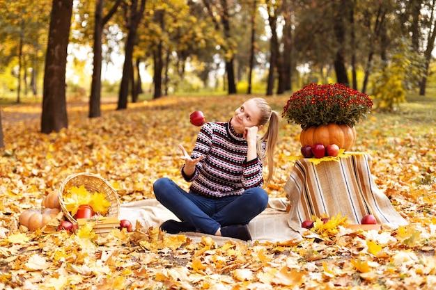 Junge frau spielt mit apfel auf einem picknick im park