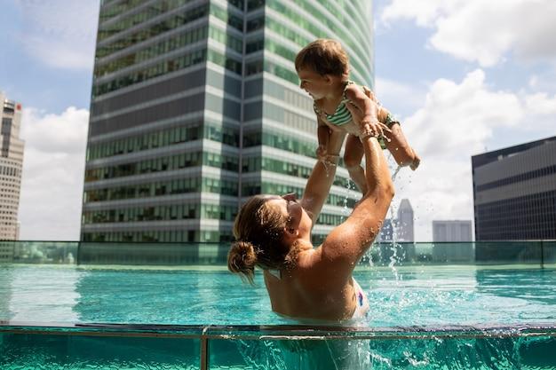 Junge frau spielt mit einem kleinen kind im pool..