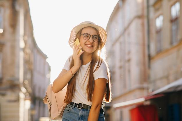Junge frau sprechen durch ihr telefon, intelligente zufällige ausstattung, hut und klare gläser, positive gefühle.