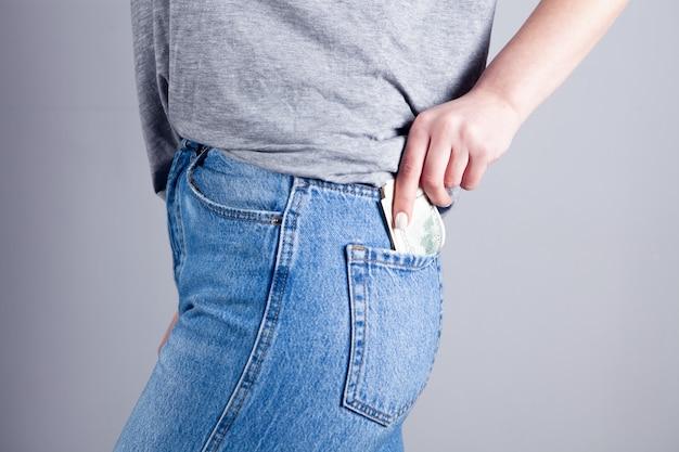 Junge frau steckt geld in ihre gesäßtasche. geld behalten
