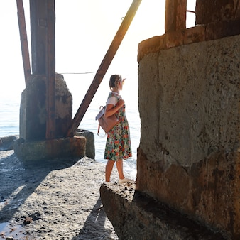 Junge frau steht auf einem alten baufälligen betonpier im sonnenlicht