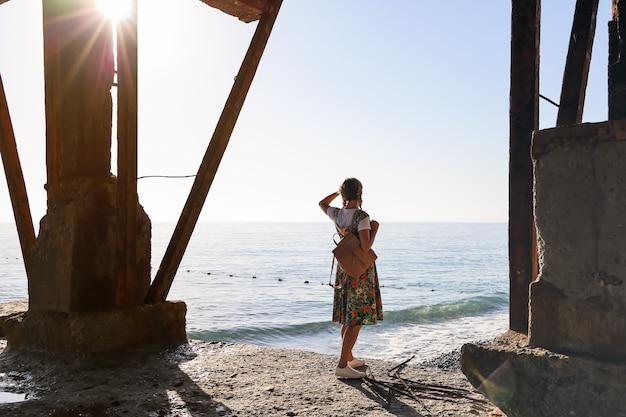 Junge frau steht auf einem alten heruntergekommenen betonpfeiler im sonnenlicht und schaut in die ferne
