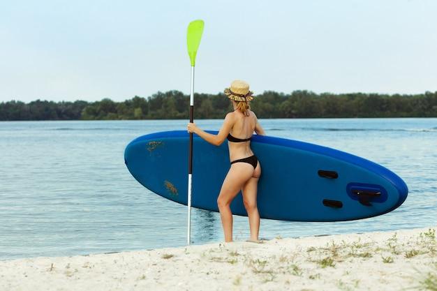 Junge frau steht auf paddle board, sup