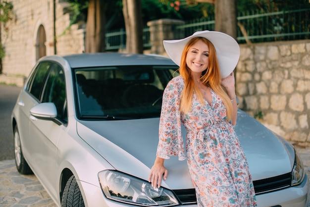 Junge frau steht in der nähe eines modernen autos auf dem hintergrund der alten europäischen stadt