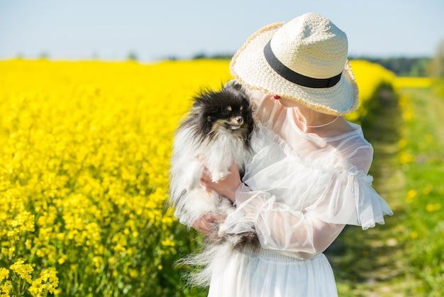 Junge frau steht in einem gelben feld mit hund