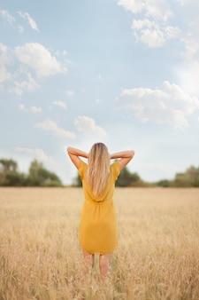 Junge frau steht mit dem rücken in einem weizenfeld und berührt ihre haare.