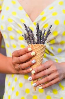 Junge frau steht mit lavendelblumen in einer waffelschale, die in einer hand hält.