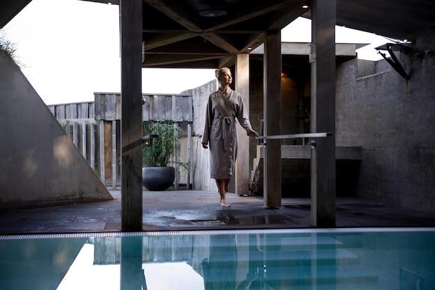 Junge frau steht neben einem pool