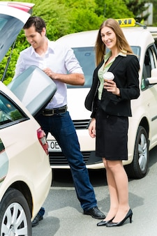Junge frau steht vor dem taxi, sie hat ihr ziel erreicht, der taxifahrer hilft mit dem gepäck