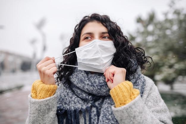 Junge frau stellt die medizinische sterile maske in einem schneebedeckten winterpark an einem kalten frostigen tag ein.