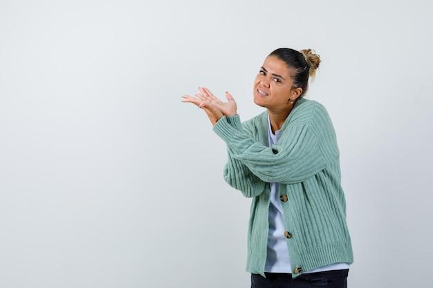 Junge frau streckt die hände nach links in weißem t-shirt und mintgrüner strickjacke und sieht glücklich aus