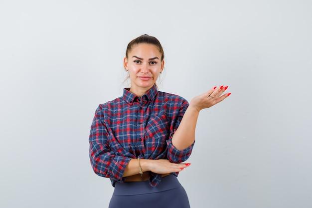 Junge frau streckt die hand in fragender geste in kariertem hemd, hose und sieht hilflos aus, vorderansicht.