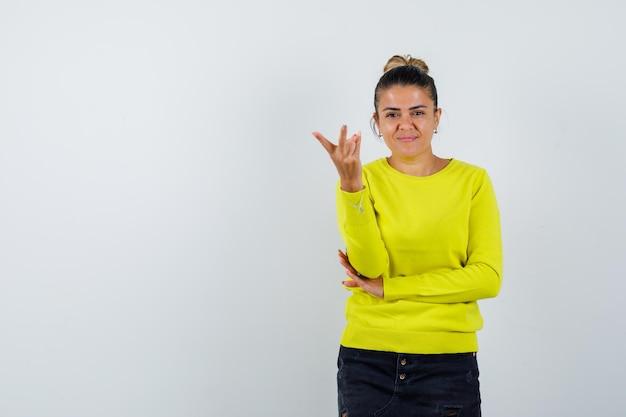 Junge frau streckt die hand in gelbem pullover und schwarzer hose in richtung kamera und sieht glücklich aus