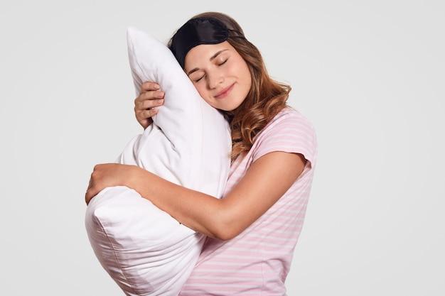 Junge frau stützt sich auf kissen, trägt pyjama und augenmaske, steht gegen weiß, hat schläfrigen ausdruck