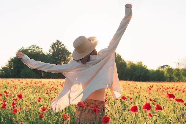 Junge frau tanzt auf mohnfeld von hinten im sonnenuntergang