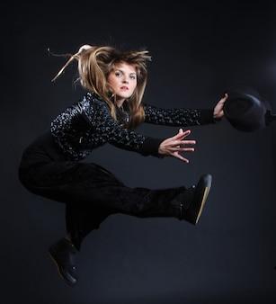 Junge frau tanzt auf schwarzem hintergrund
