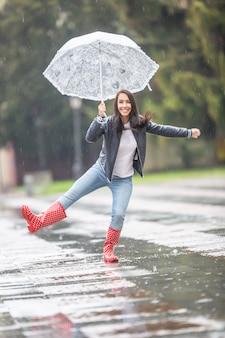 Junge frau tanzt im regen im park, hält einen regenschirm und trägt regenstiefel.
