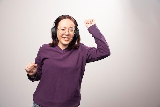 Junge frau tanzt und hört musik in kopfhörern auf einem weiß. foto in hoher qualität