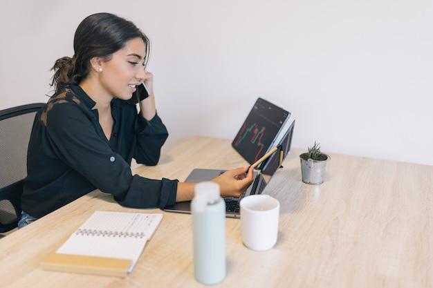 Junge frau telefoniert, während sie mit einem stift auf den bildschirm zeigt