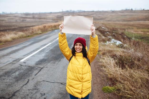 Junge frau tourist, die gelbe jacke und roten hut trägt, steht mit einem leeren plakatpapier auf der seite einer leeren winterstraße.