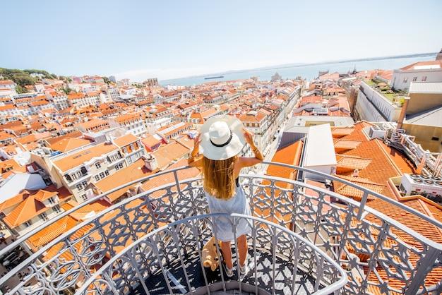 Junge frau tourist genießen schöne stadtbild draufsicht auf die altstadt während des sonnigen tages in der stadt lissabon, portugal