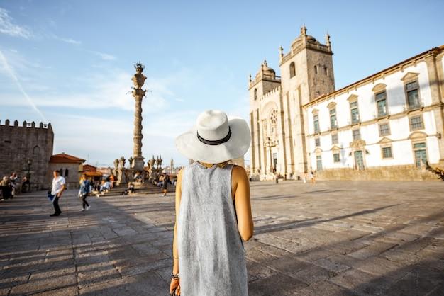 Junge frau tourist in sonnenhut, der während des sonnenuntergangs in portugal vor der hauptkathedrale in der stadt porto steht?