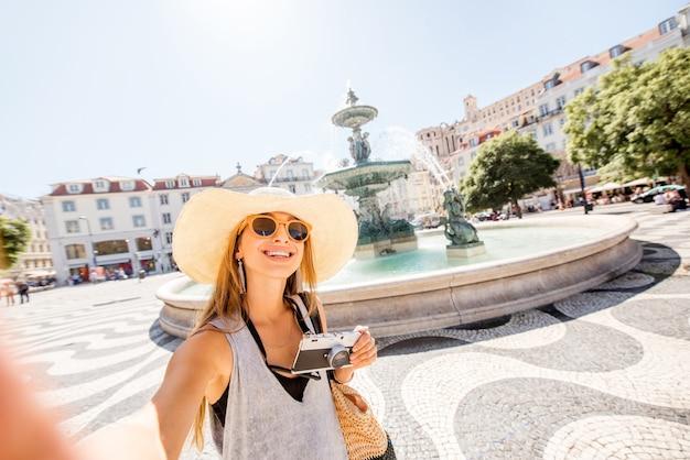 Junge frau tourist machen selfie-porträt in der nähe des brunnens auf dem pedro-platz in der altstadt von lissabon, portugal