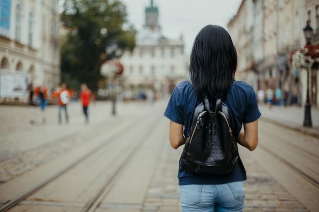 Junge frau tourist mit einem lederrucksack zu fuß in einer alten stadt lemberg. platz für text