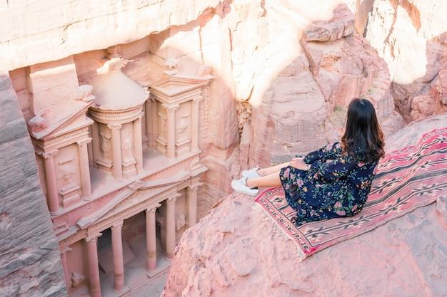 Junge frau tourist sitzt auf einer klippe nach erreichen der spitze, al khazneh in der antiken stadt petra, jordanien