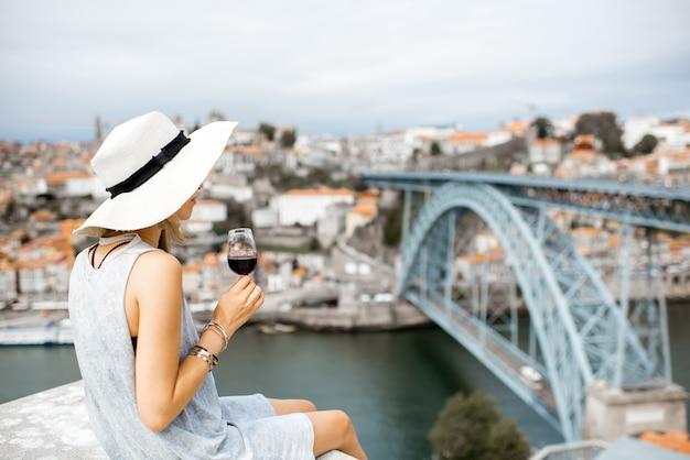 Junge frau tourist sitzt mit einem glas porto wein auf der terrasse mit blick auf die stadt porto in portugal