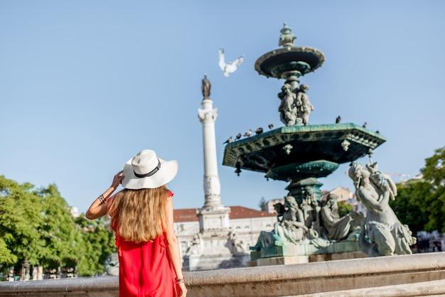 Junge frau tourist steht auf dem rossio-platz in der nähe des brunnens während des morgenlichts reisen in lissabon, portugal