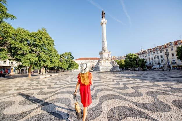 Junge frau tourist zu fuß auf dem rossio-platz mit pedro-statue im morgenlicht in lissabon, portugal
