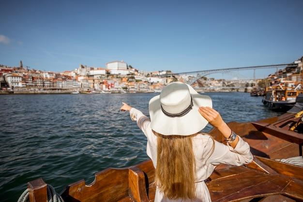 Junge frau tourist zurück auf dem boot am fluss douro in der stadt porto, portugal