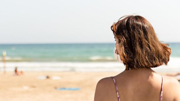Junge frau trägt eine gesichtsmaske am strand - pandemie