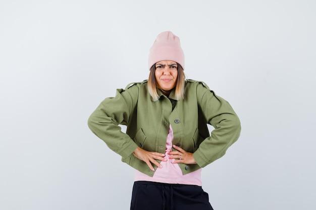 Junge frau trägt eine jacke und einen rosa hut