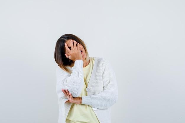 Junge frau trägt eine weiße strickjacke, die ihr gesicht bedeckt