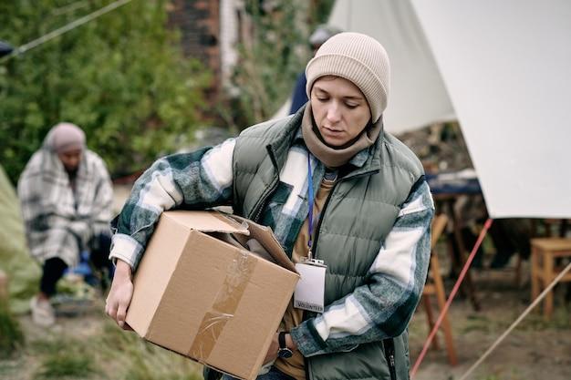 Junge frau trägt kiste mit kleidung für flüchtlinge